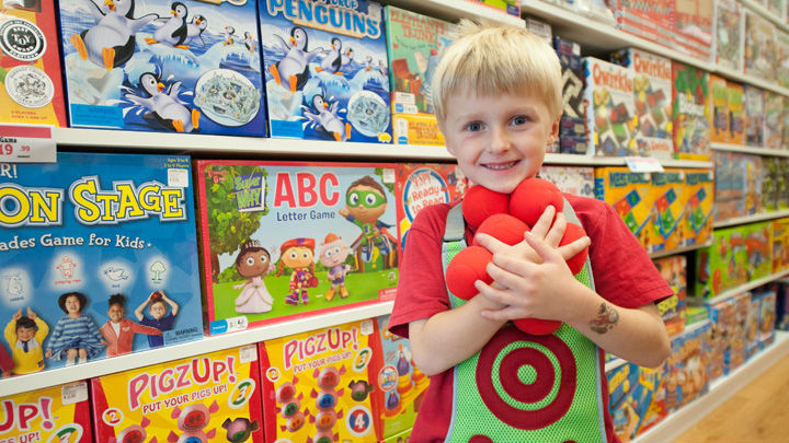 boy with red balls in learning express toy store