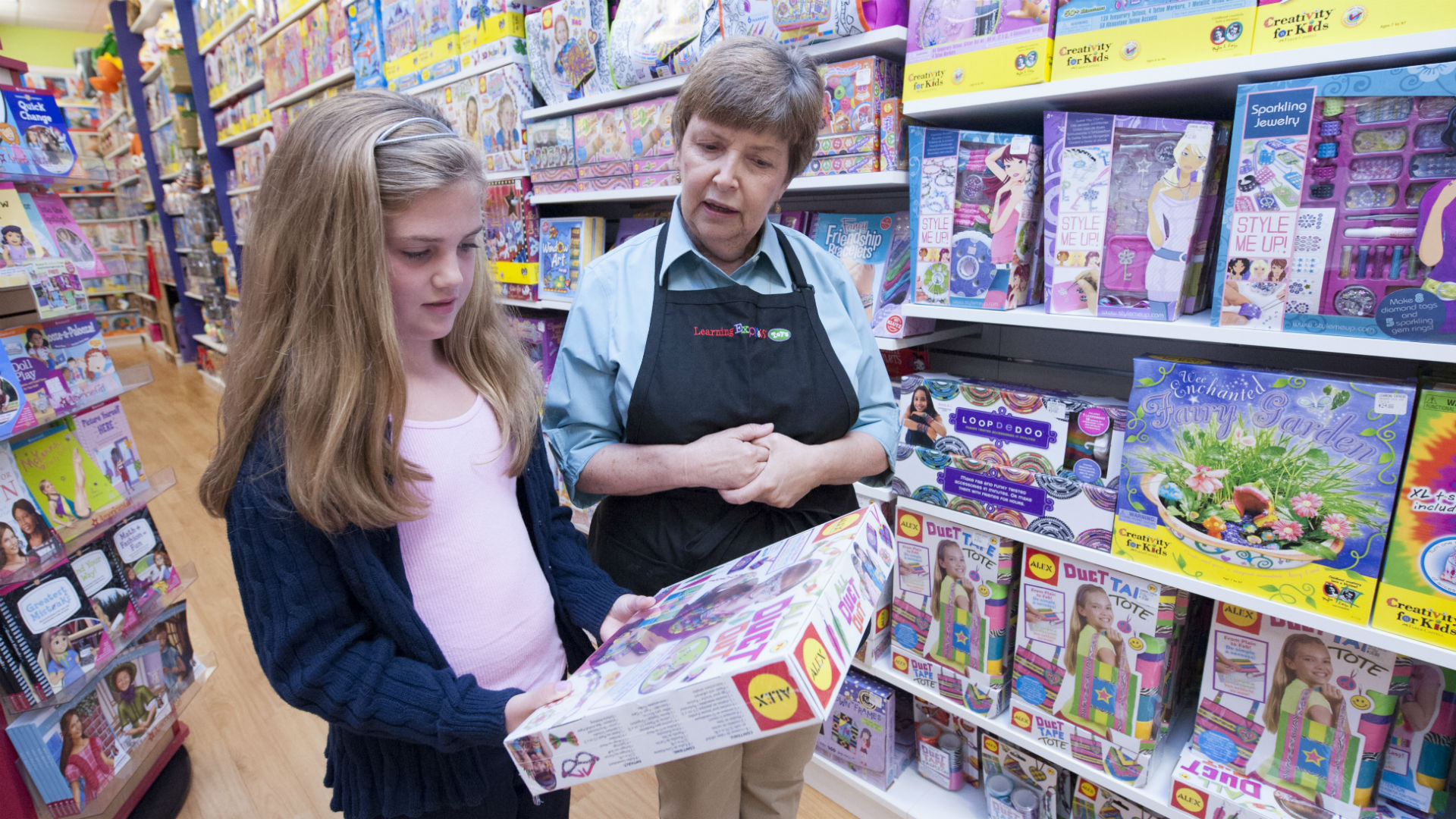 woman helping girl pick out toy at learning express toy store