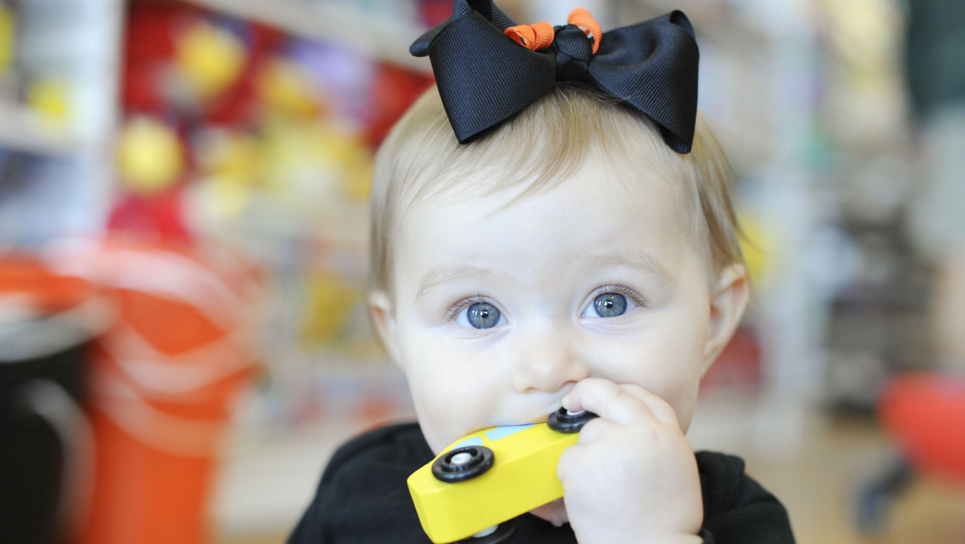baby girl with car in mouth and black bow